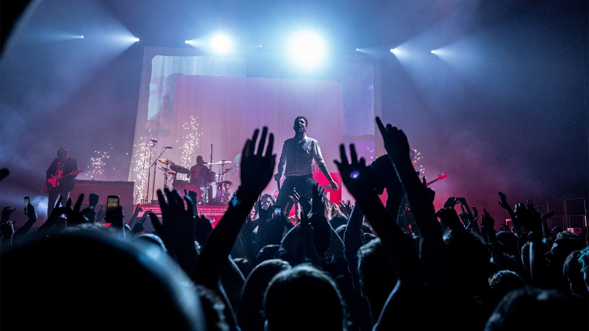 A band perform on stage, with audience hands waving and clapping. Photo by Ben Morse.